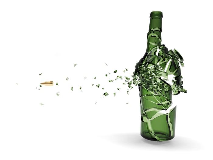 Bullet shattering a green beer bottle