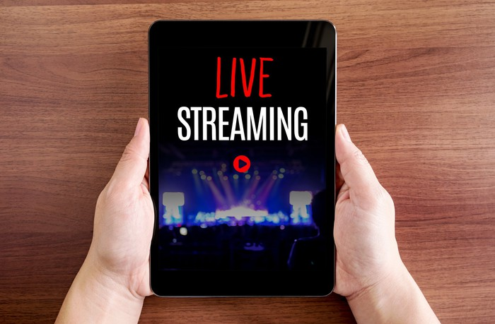 Two hands holding tablet with Live streaming and play icon