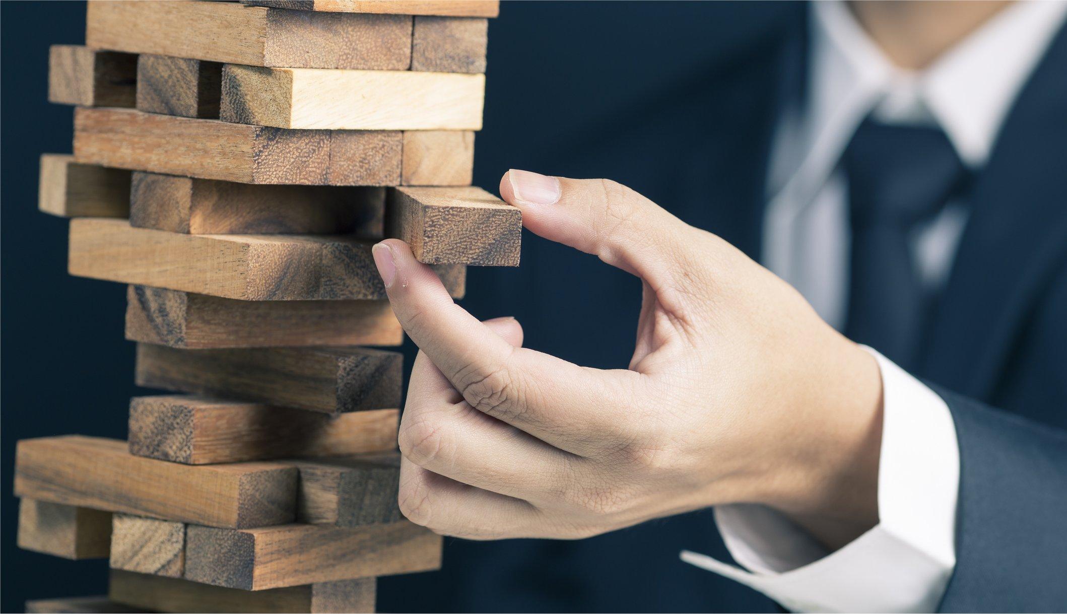A businessman removes a Jenga block.