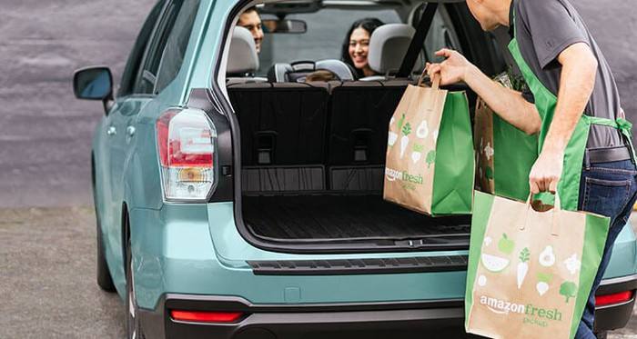 An AmazonFresh Pickup attendant puts groceries in a trunk.