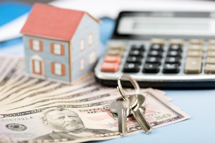 Miniature house, calculator, house keys, and money.
