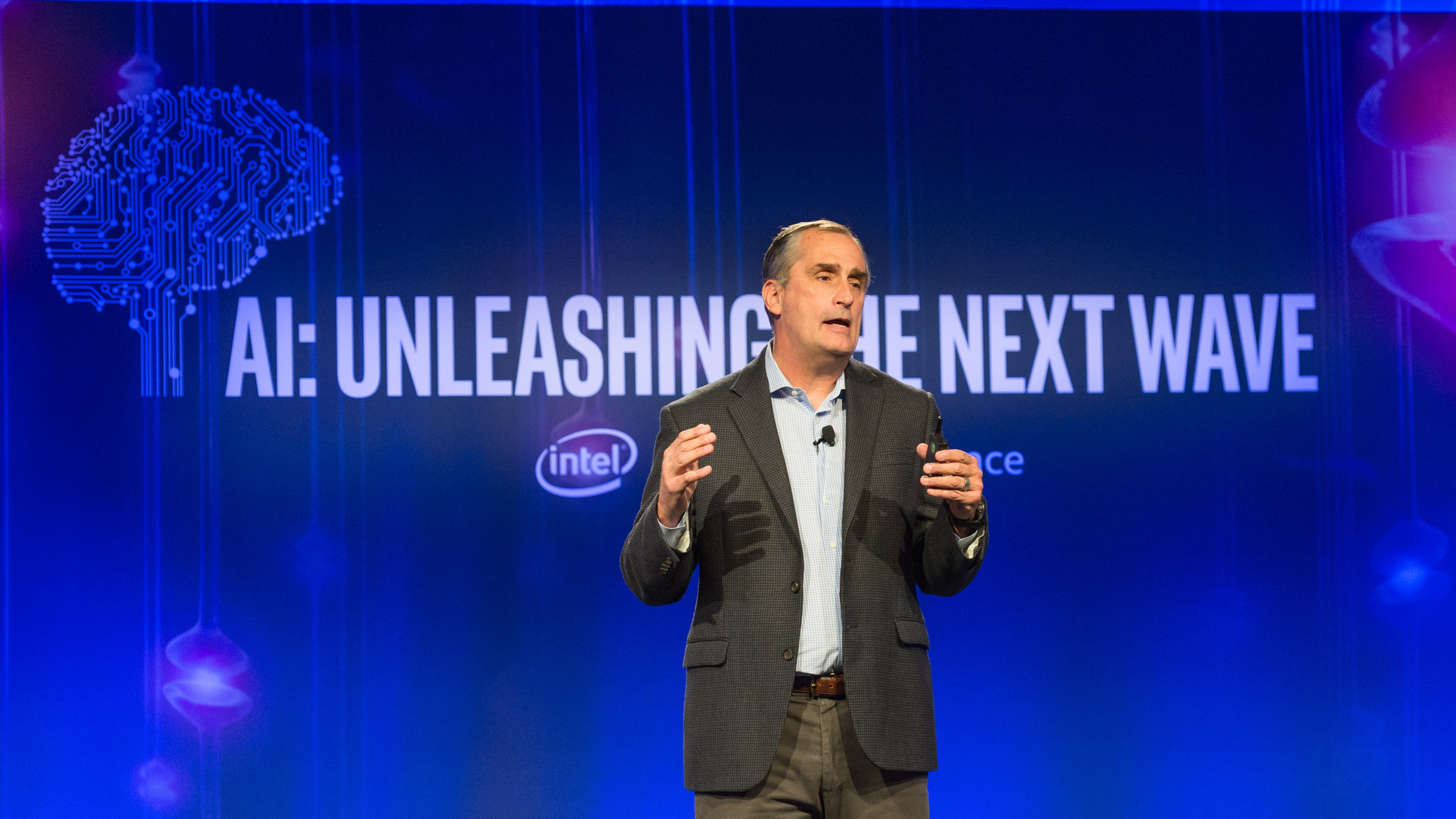 "Intel CEO Brian Krzanich on stage with ""AI: Unleashing the Next Wave"" projected behind."