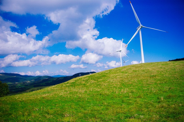 A series of wind turbines on rolling, grassy hills.