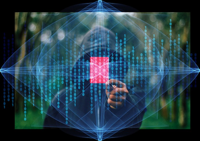 Hacker in hoodie with stylized binary code.