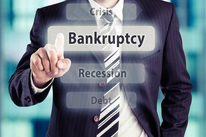 """A businessman pressing the """"bankruptcy"""" key on a digital board."""
