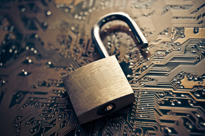 A padlock placed on a circuit board to symbolize cybersecurity.