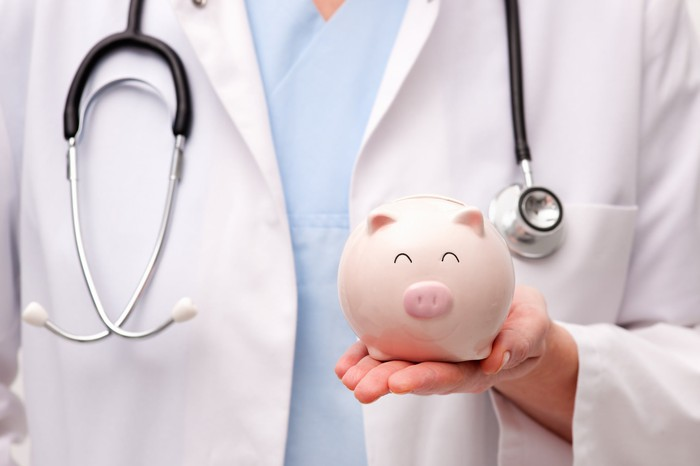 A doctor holding a piggy bank.
