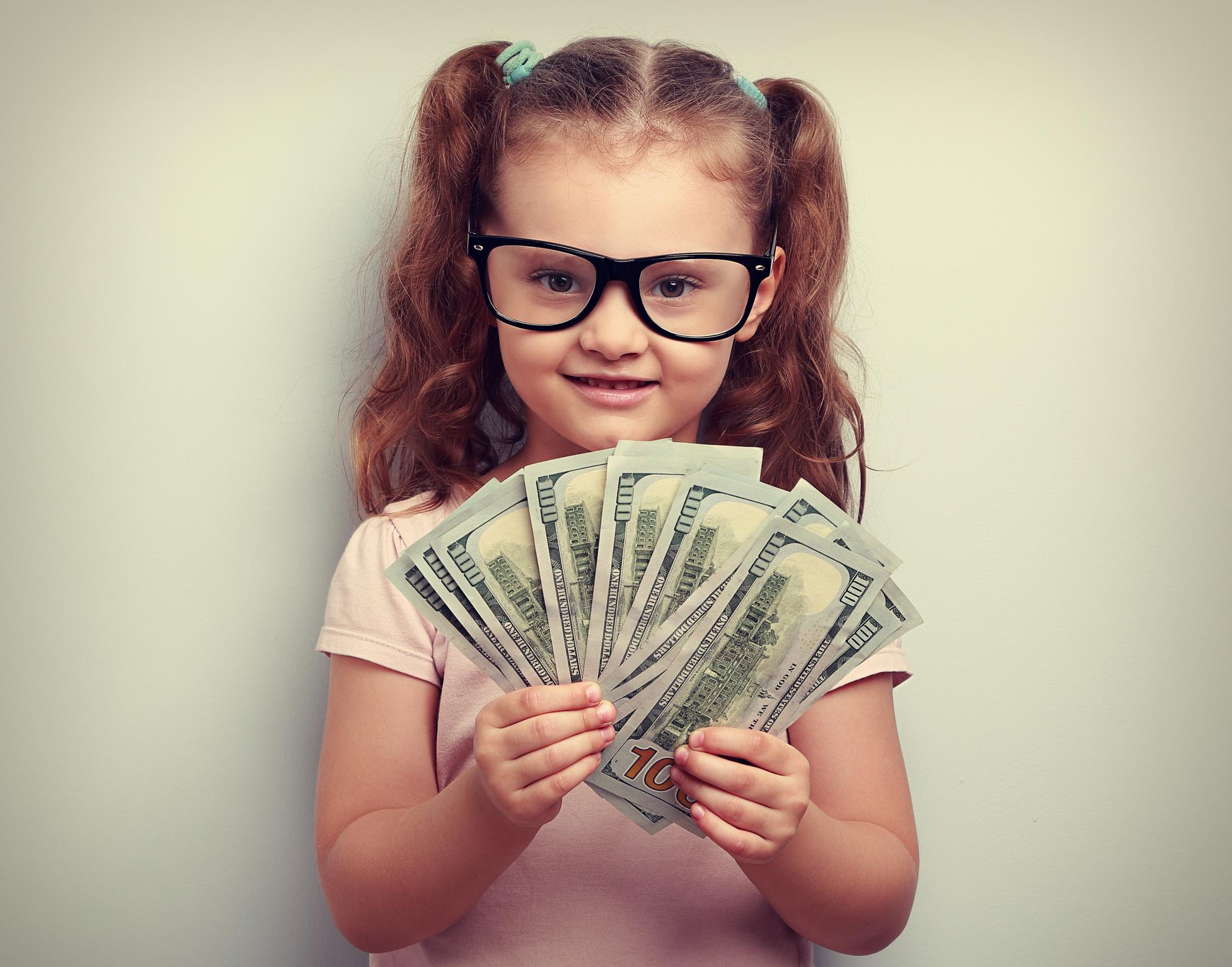 A little girl holdings many dollar bills.