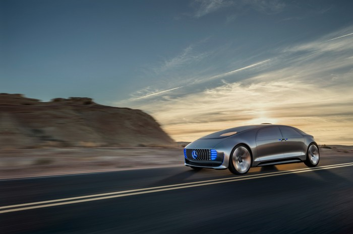 The Mercedes concept vehicle, a futuristic-looking silver sedan, is shown on a country road.