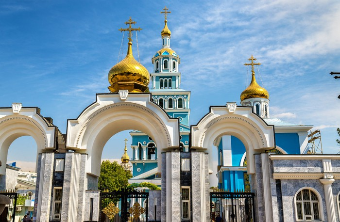 The gold domes of the Dormition Cathedral shine against a bright blue sky.