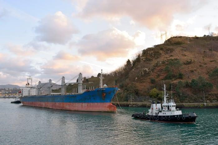 Tug boat pulling a bulk cargo ship across the water.
