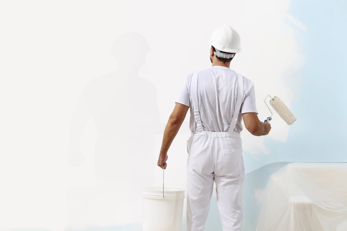 Painter painting a wall with white paint.