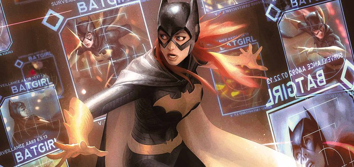 DC Comics character Batgirl standing in front of a screen that has images of her on it.