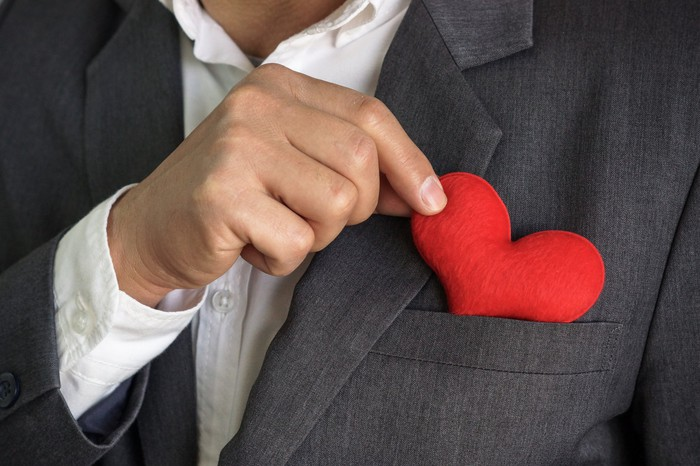 A businessman putting a red heart into his suit pocket.
