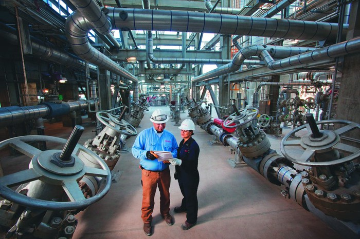 A man and woman in hard hats stand among oil pipes.