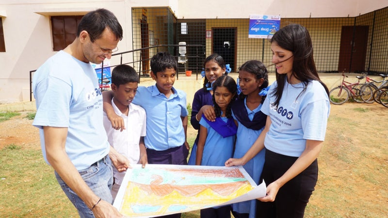 A few Goldman Sachs employees standing around some children and a drawing in Bangalore.