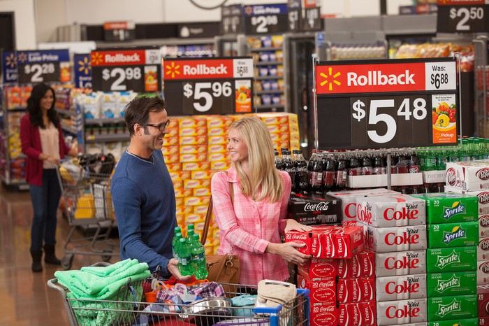 "A couple smiles while shopping a ""roll back"" deal at a Wal-mart store."