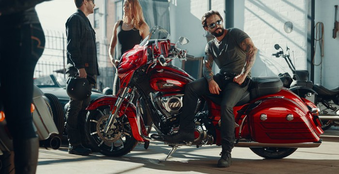 A male model wearing sunglasses sits on the new Indian Chieftain Elite in candy-apple red on a busy showroom floor