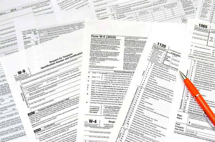 An assortment of tax forms, and a pen.
