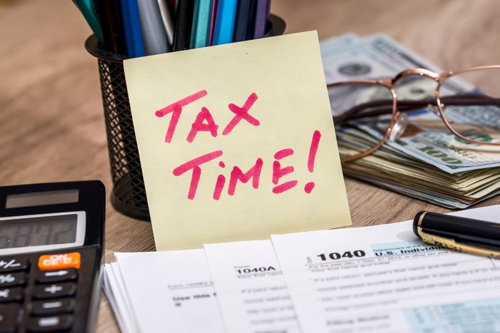 """Tax forms and calculator with a small note reading """"tax time!"""""""