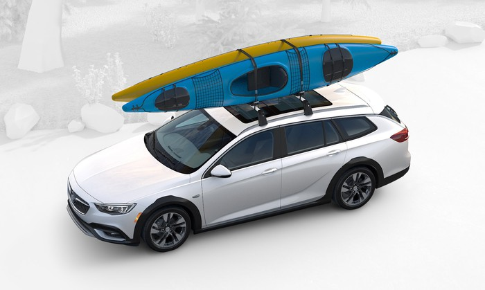 A white Regal TourX with a blue kayak on its roof is shown from above.