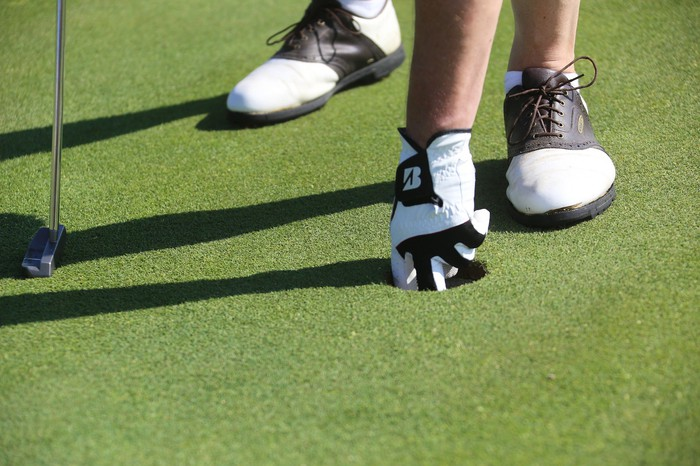Two feet in golf shoes on putting green, placing ball