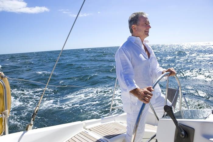 Older man at helm of boat on ocean