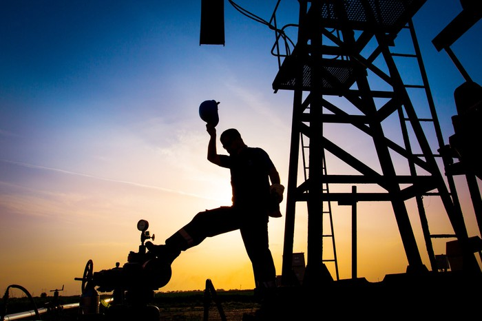 An oil worker in silhouette against an oil well.