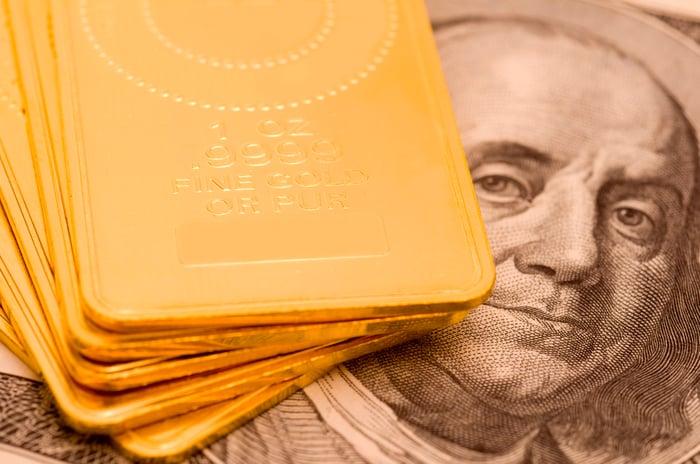 Gold ingots sitting atop a hundred dollar bill.