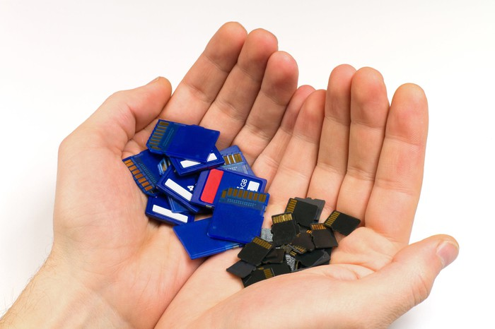 A man holds a lot of SD and Micro SD cards in his hands.