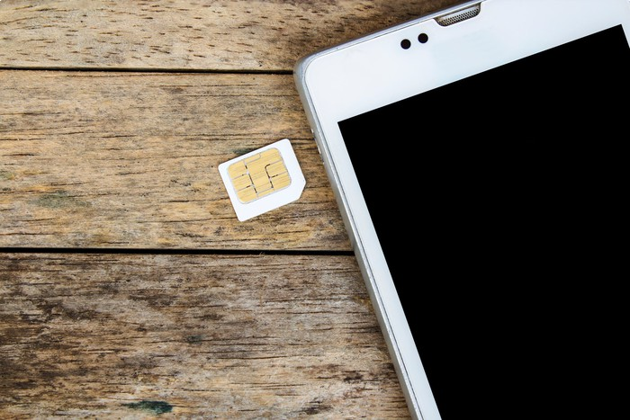 A SIM card placed next to a smartphone.