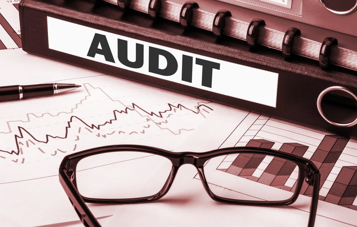 Documents and glasses with an audit sign adjacent