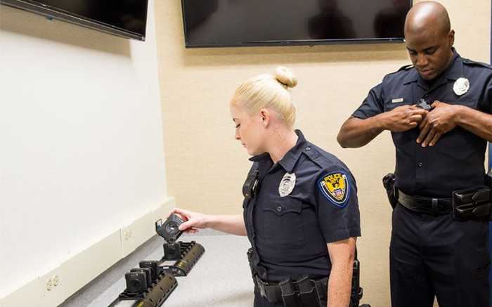 Police officers putting on Axon body cameras.