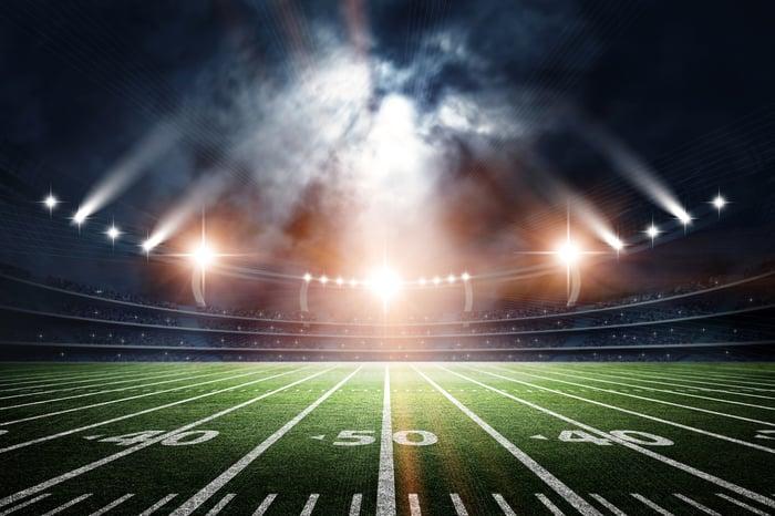 Brightly lit American football stadium at night.