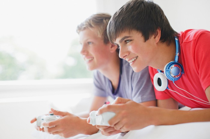 Two teenage boys playing video games.