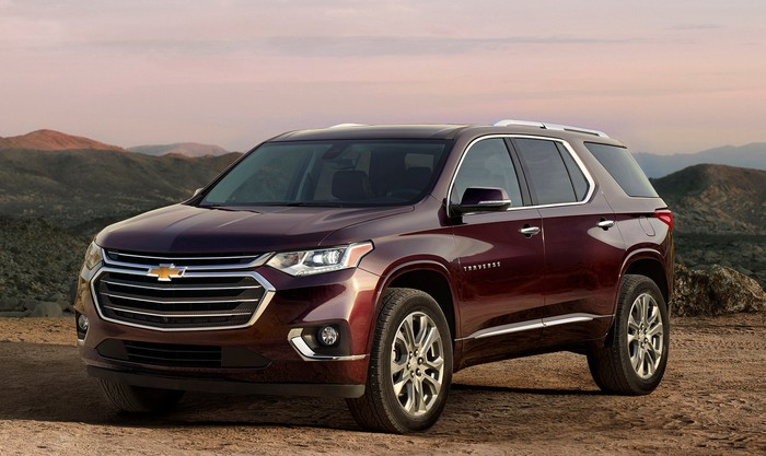 A dark red Traverse, a big crossover SUV, with mountains in the background.