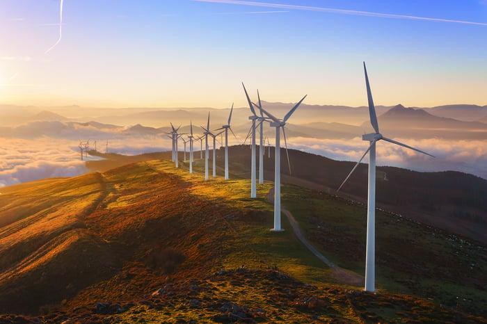 Wind turbines on a hill at sunrise.