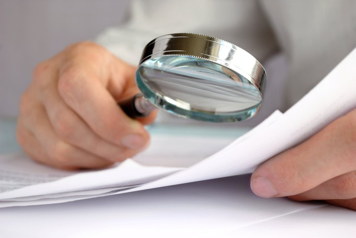 Hand holding a magnifying glass, examining a sheet of paper.