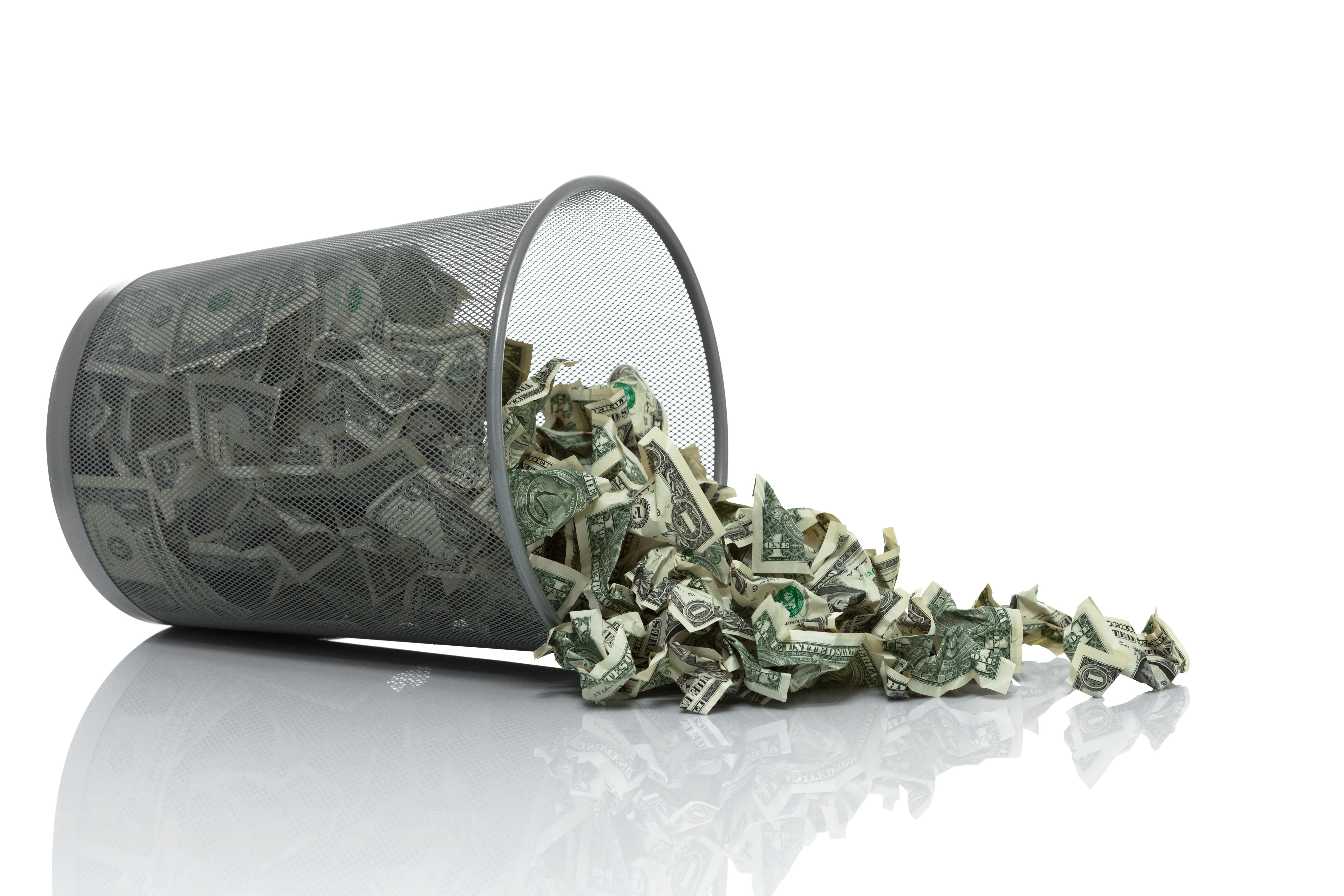 Trash can spilling money.