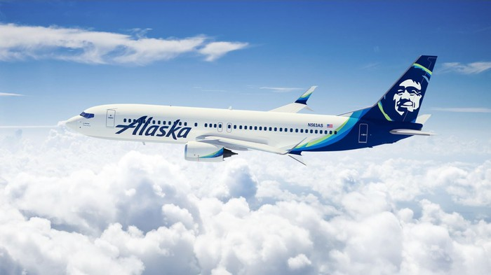 An Alaska Airlines plane, flying above the clouds.