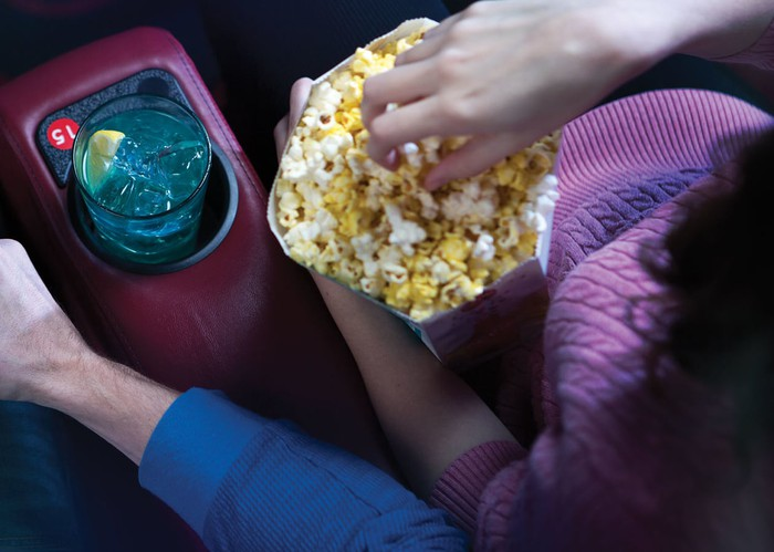 Hand in popcorn and drink in cup-holder in movie theater seat