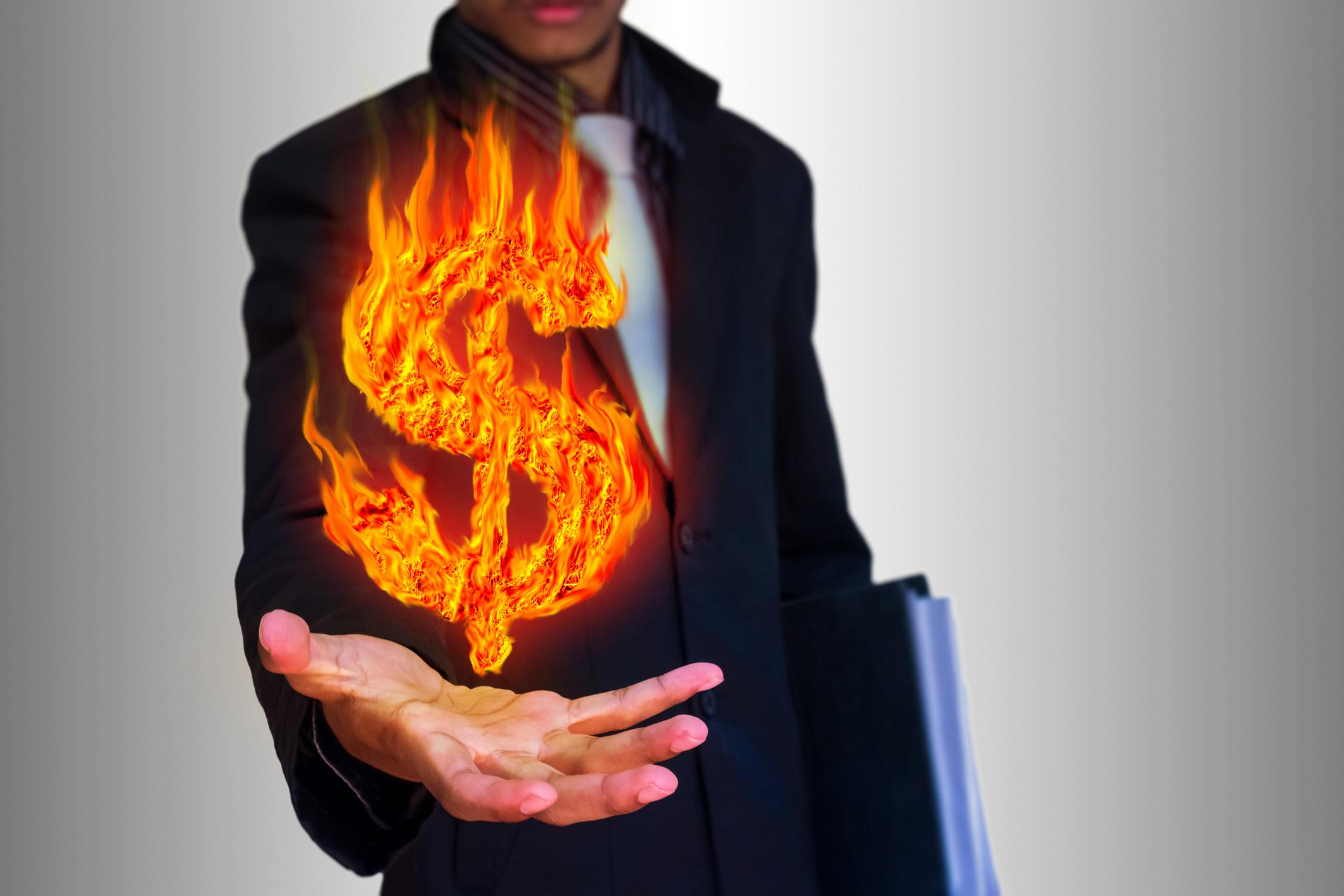 Businessman holding a flaming dollar symbol.