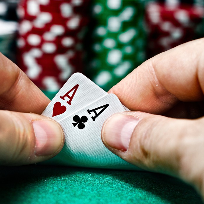 A poker player revealing that he/she has two aces.