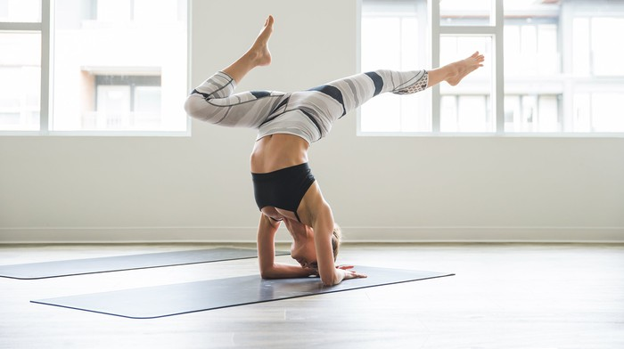 A woman stands on her head in a yoga pose wearing lululemon athletica clothing.