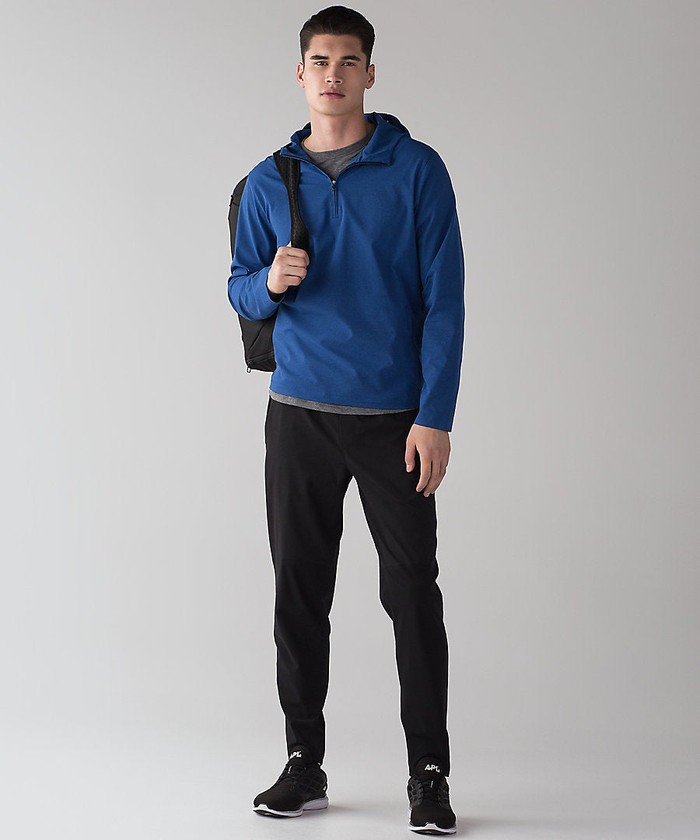 A model wearing a blue jacket, black pants, and a black backpack all made by lululemon.