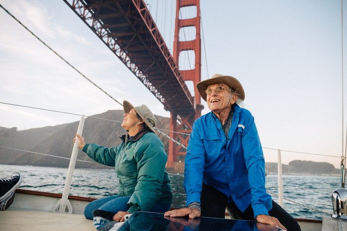 Two people on a sailboat under the Golden Gate Bridge in San Francisco.
