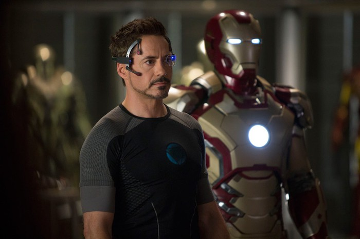 Tony Stark in front of his Iron Man armour.