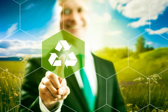 A man pointing with his finger to a recycling logo