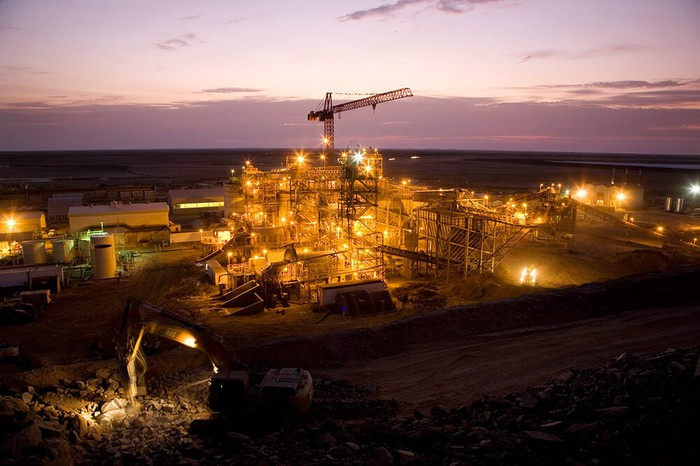 A view of the Tasiast mine, illuminated against a dimly lit sky.