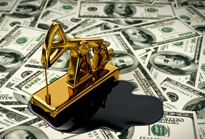 A golden pumpjack and spilled oil on dollars.